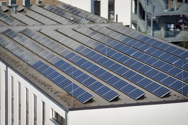 Große Gruppe von Solarpaneelen auf dem Dach eines Industriegebäudes – Foto