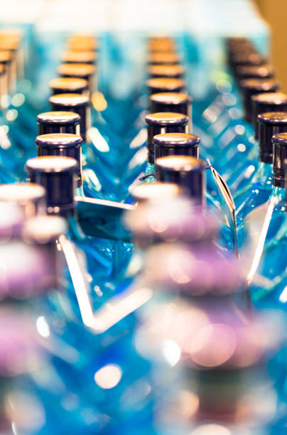 Large group of spirit bottles on shelves in shop ready for sale stock photo