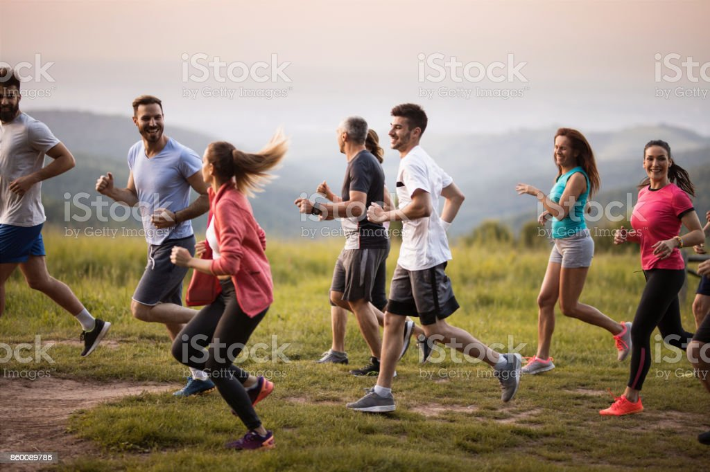 Large group of sports people running through nature and communicating. stock photo