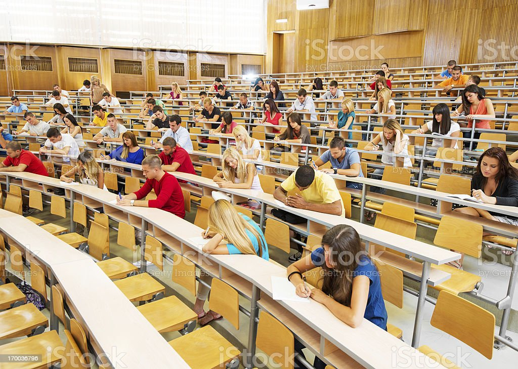 Large group of students doing exam. stock photo