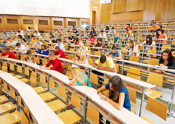 Large group of students doing exam. Group of college students at the university amphitheatre, they are sitting and doing an exam.   amphitheater stock pictures, royalty-free photos & images