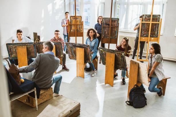große gruppe von schülern, die eine kunstklasse mit ihrem lehrer in einem atelier haben. - high school bilder stock-fotos und bilder