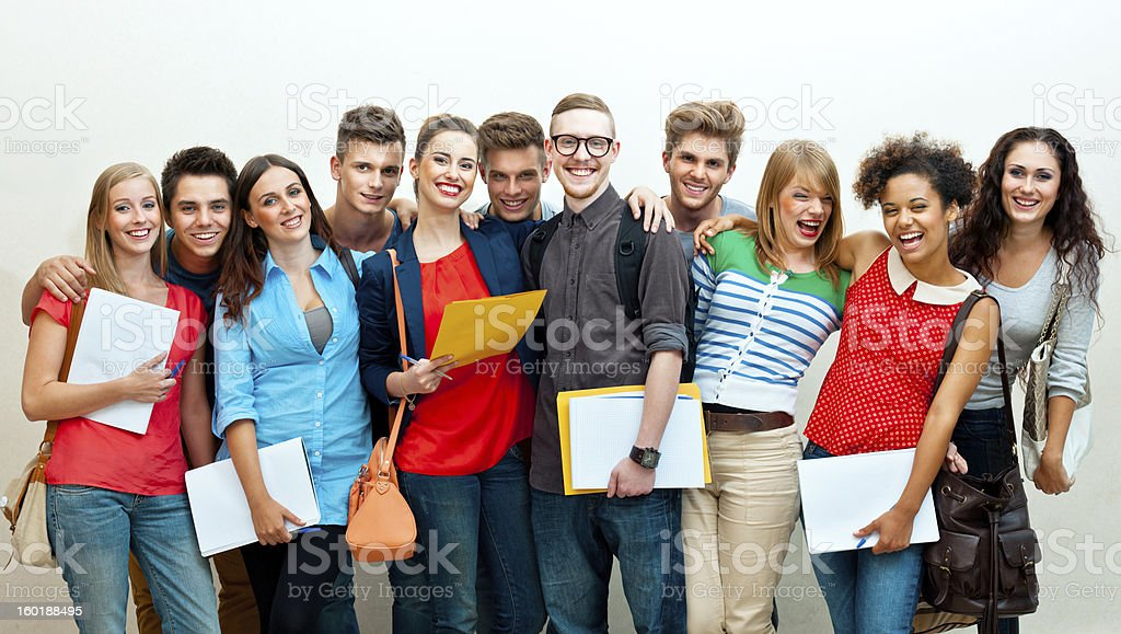 Large group of students Large group of diverse high school students standing against white wall, embracing and laughing at camera.  20-24 Years Stock Photo