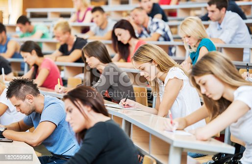 istock Large group of students writing in notebooks. 182059956
