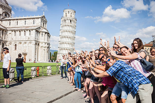 Large group of tourist having fun in Pisa Pisa, Italy - June 22, 2015: Large group of tourists posing and having fun doing funny portraits in front of the Leaning Tower of Pisa during a beautiful summer day. pisa stock pictures, royalty-free photos & images