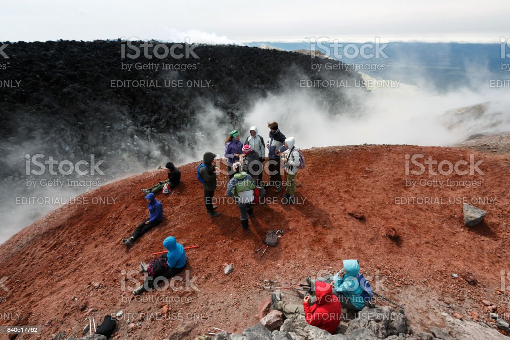 Large group of tourists and travelers in crater of active volcano stock photo