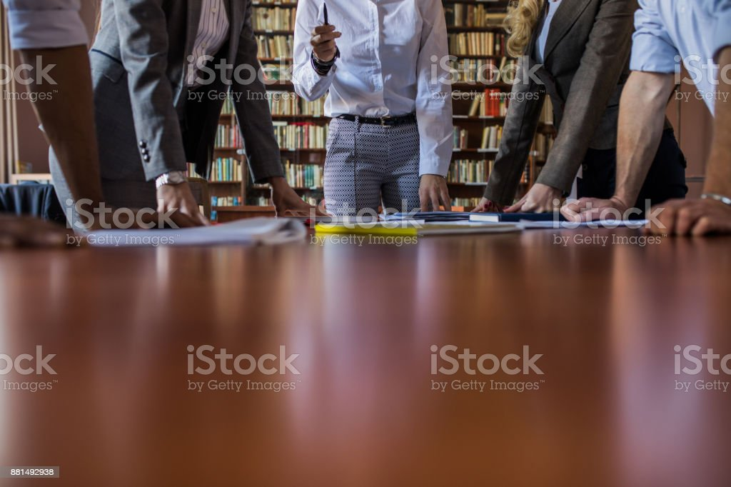 Large group of unrecognizable business people having a meeting in the office. stock photo