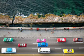 Large group of vintage American cars speeding along the Malecon in Havana, Cuba, motion blur, people sitting on sea wall, Caribbean Sea is visible in the background, elevated view.