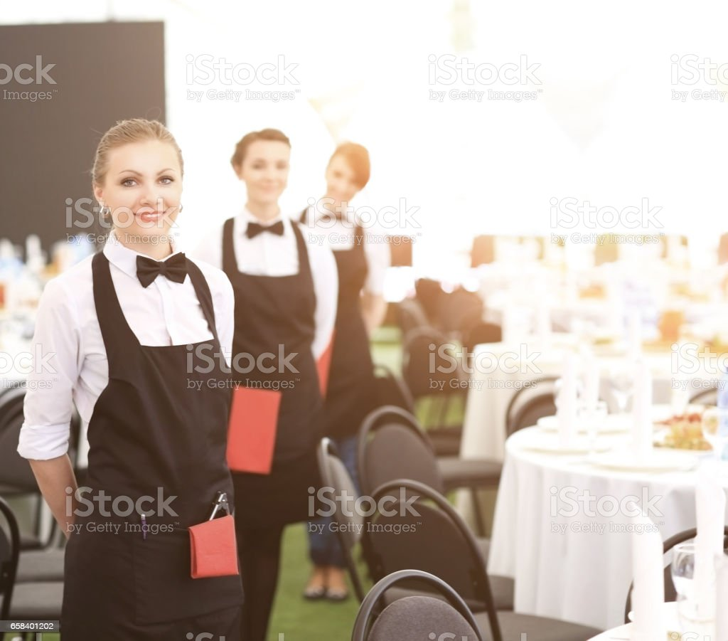A large group of waiters and waitresses next to served tables stock photo