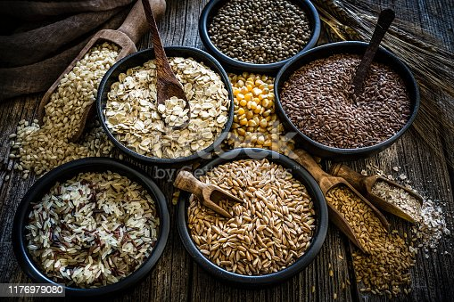 High angle view of wholegrain and cereal composition shot on rustic wooden table. This type of food is rich of fiber and is ideal for dieting. The composition includes oat flakes, brown rice, dried corn,spelt, hemp seeds and flax seeds. Predominant color is brown. XXXL 42Mp studio photo taken with SONY A7rII and Zeiss Batis 40mm F2.0 CF