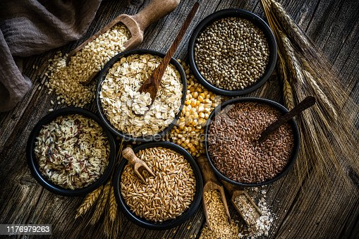 Top view of wholegrain and cereal composition shot on rustic wooden table. This type of food is rich of fiber and is ideal for dieting. The composition includes oat flakes, brown rice, dried corn,spelt, hemp seeds and flax seeds. Predominant color is brown. XXXL 42Mp studio photo taken with SONY A7rII and Zeiss Batis 40mm F2.0 CF