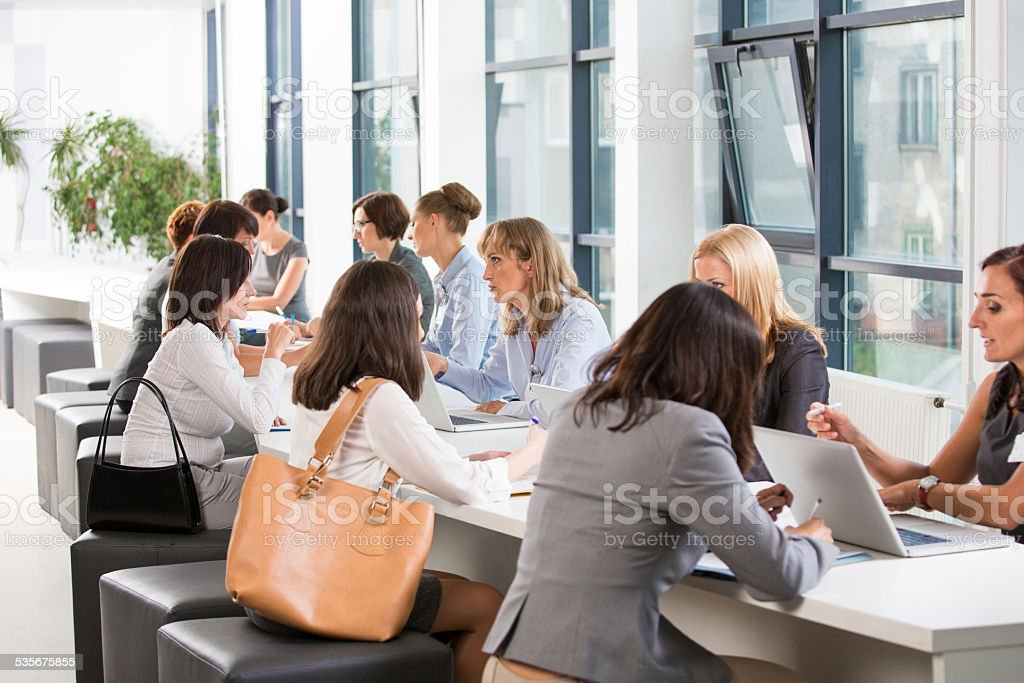 Large group of women at job fair Large group of women attending a job fair, working together and discussing in an office. 2015 Stock Photo