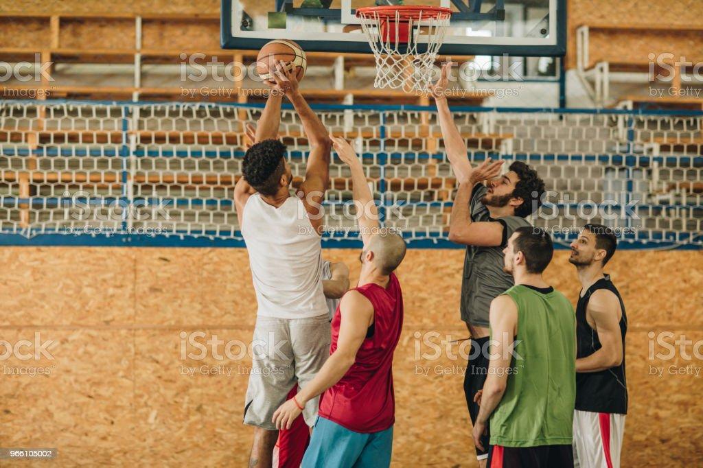 Stor grupp av unga atletiska män som spelar basket. - Royaltyfri Afroamerikanskt ursprung Bildbanksbilder