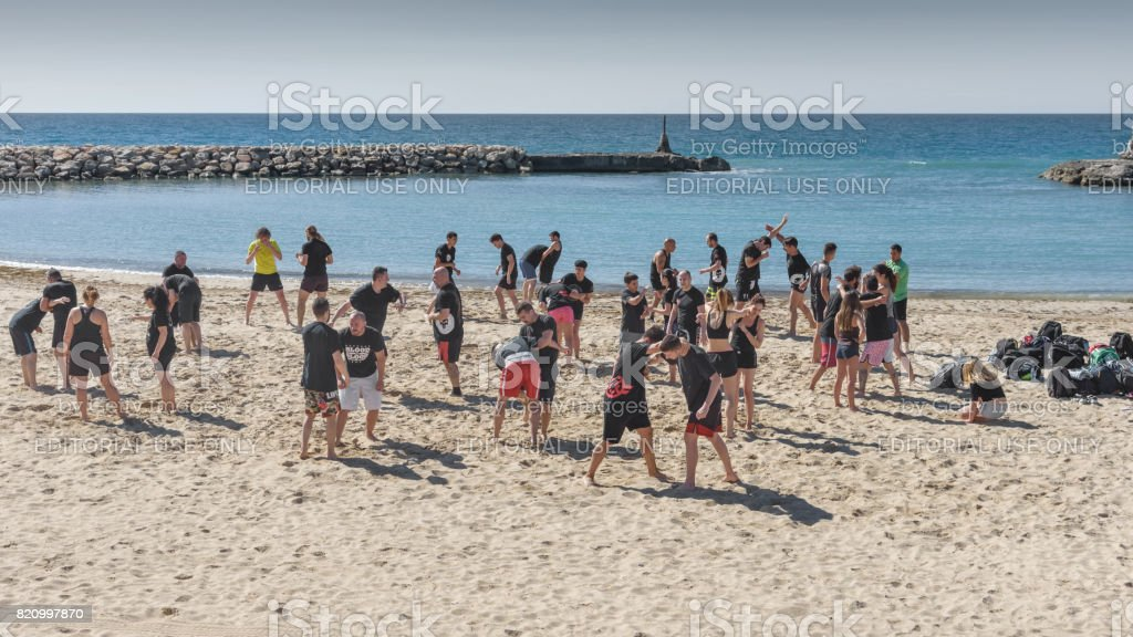 Large group of young girls and boys, are engaged in wrestling on the seashore. General plan stock photo