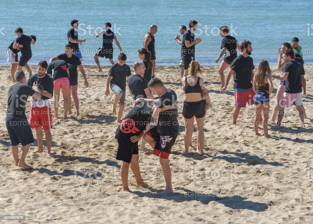 Large group of young people, girls and boys, are engaged in wrestling on the seashore stock photo