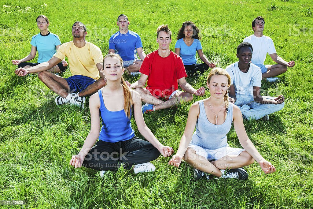 Large group of young people meditating. royalty-free stock photo