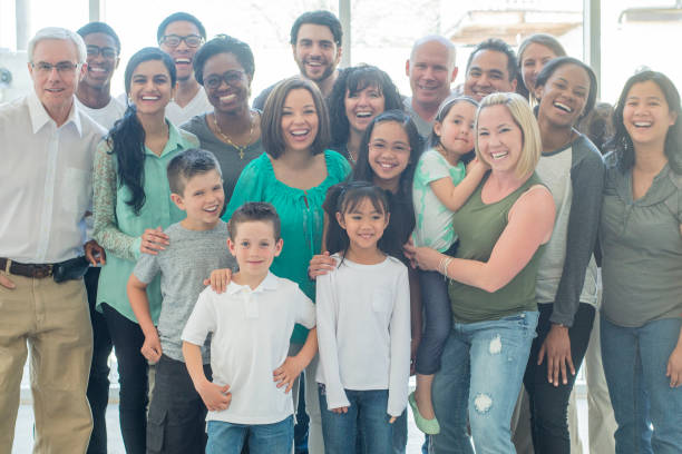 Large Group A multi-ethnic group of adults and children are indoors. They are wearing casual or semiformal clothing. They are posing and smiling for a large group photo. global village stock pictures, royalty-free photos & images