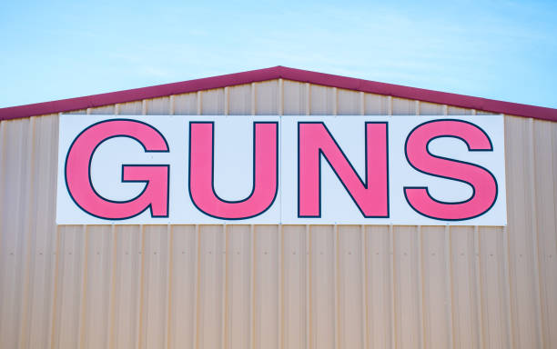 Large GUNS sign on the outdoor of a Gun Store Large GUNS sign on the outdoor of a Gun Store gun shop stock pictures, royalty-free photos & images
