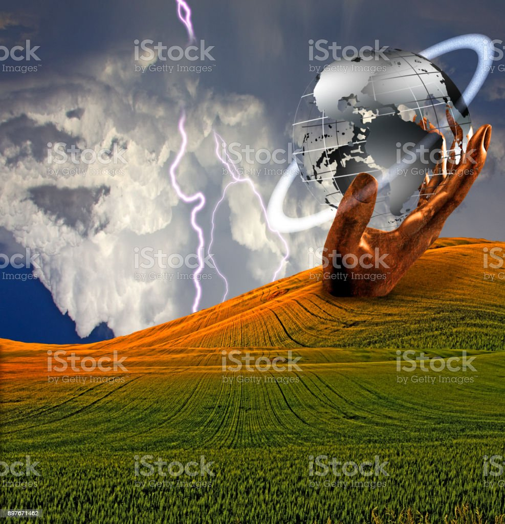 Large hand and earth sculpture in landscape stock photo