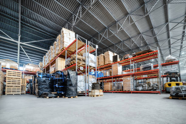 Large hangar warehouse industrial and logistics companies Large hangar warehouse industrial and logistics companies. Warehousing on the floor and called the high shelves. Toning the image. distribution center stock pictures, royalty-free photos & images