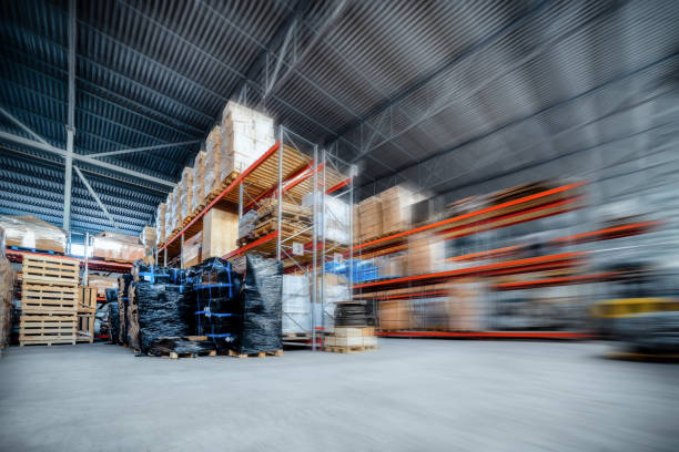 Large hangar warehouse industrial and logistics companies Large hangar warehouse industrial and logistics companies. Warehousing on the floor and called the high shelves. Toning the image. Motion blur effect. distribution center stock pictures, royalty-free photos & images