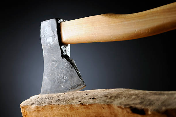 Large, heavy steel ax with wooden handle stuck in log stock photo