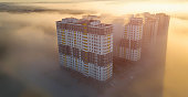 Concept, powdery and cozy, large high-rise buildings in the fog at dawn. Long shadows from buildings.