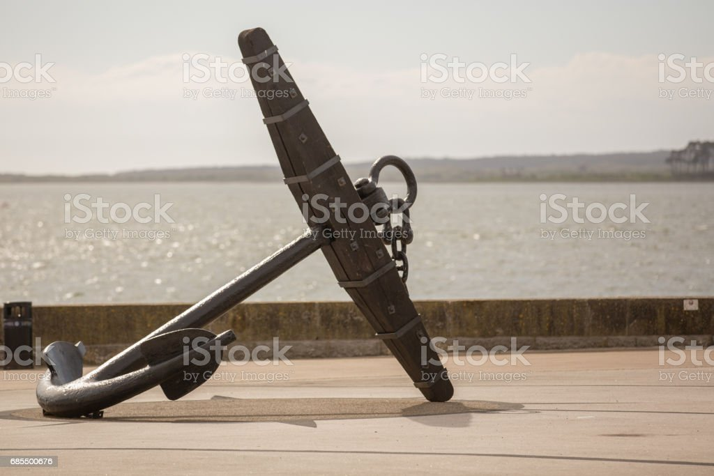 Large historic anchor lying on its side on harbour stock photo