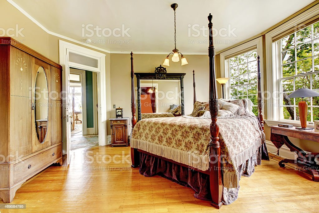 Large historical Inn room interior - bedroom with antique bed. stock photo
