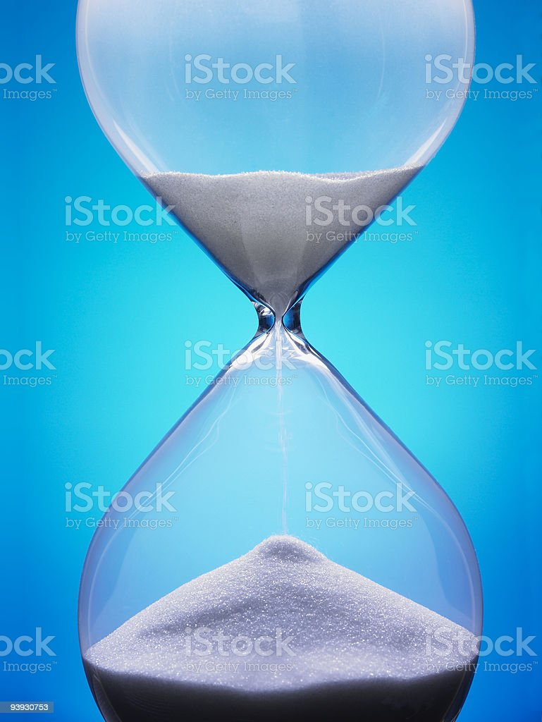 Large hourglass with white sand against a blue background A macro shot of an hourglass. Blue Stock Photo