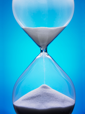 Large Hourglass With White Sand Against A Blue Background Stock Photo - Download Image Now