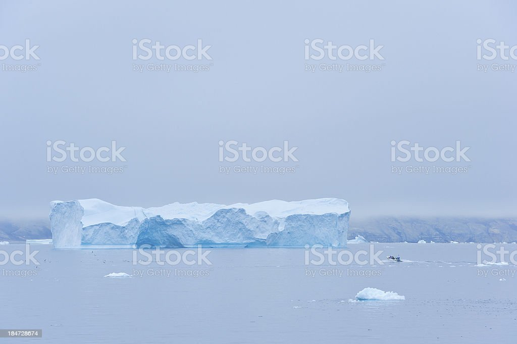 Large iceberg and small boat in Greenland stock photo