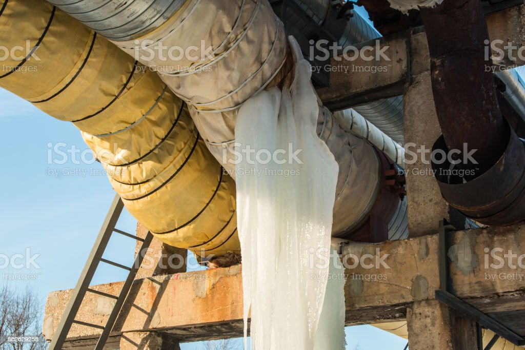 large icicle on a water pipe and loss of heat in winter stock photo