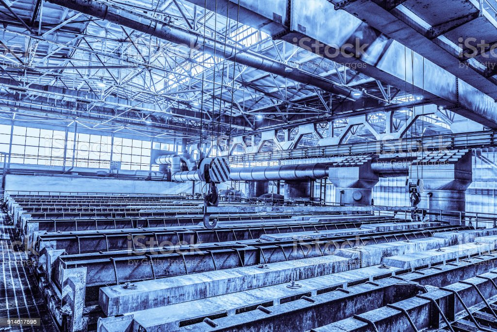Large industrial bath for galvanizing steel metal products. Hooks of overhead cranes. Unified standard typical span prefabricated of a steel frame production building. Background in blue tone. stock photo