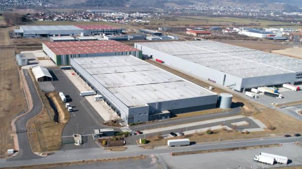 grote industriële gebouwen daken en vrachtwagens - industriegebied stockfoto's en -beelden