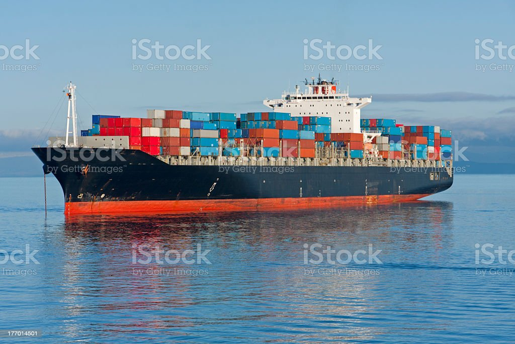 A large industrial container ship sailing through the ocean stock photo