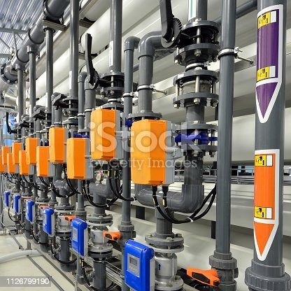 istock Large industrial water treatment and boiler room. Shiny steel metal pipes and blue pupms and valves. 1126799190
