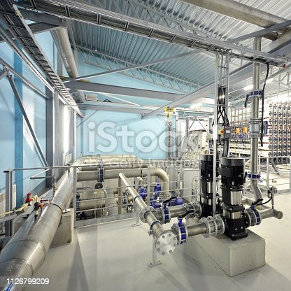 istock Large industrial water treatment and boiler room. Shiny steel metal pipes and blue pupms and valves. 1126799209