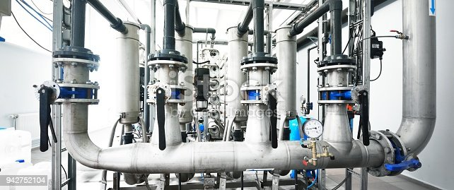 istock Large industrial water treatment and boiler room. Shiny steel metal pipes and blue pupms and valves. 942752104