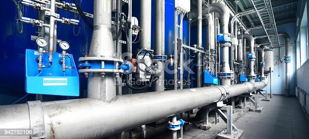 istock Large industrial water treatment and boiler room. Shiny steel metal pipes and blue pupms and valves. 942752106