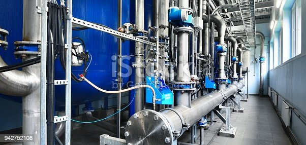istock Large industrial water treatment and boiler room. Shiny steel metal pipes and blue pumps and valves. 942752108
