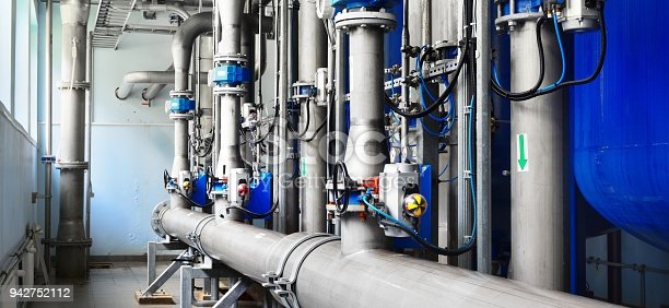 istock Large industrial water treatment and boiler room. Shiny steel metal pipes and blue pumps and valves. 942752112
