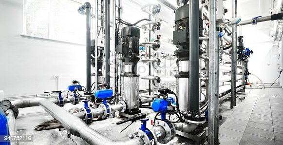 istock Large industrial water treatment and boiler room. Shiny steel metal pipes and blue pupms and valves. 942752116