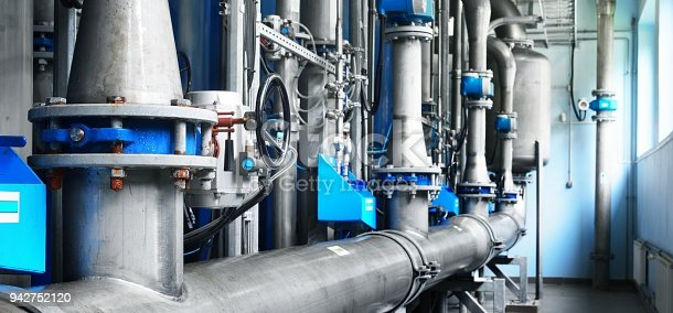 istock Large industrial water treatment and boiler room. Shiny steel metal pipes and blue pumps and valves. 942752120
