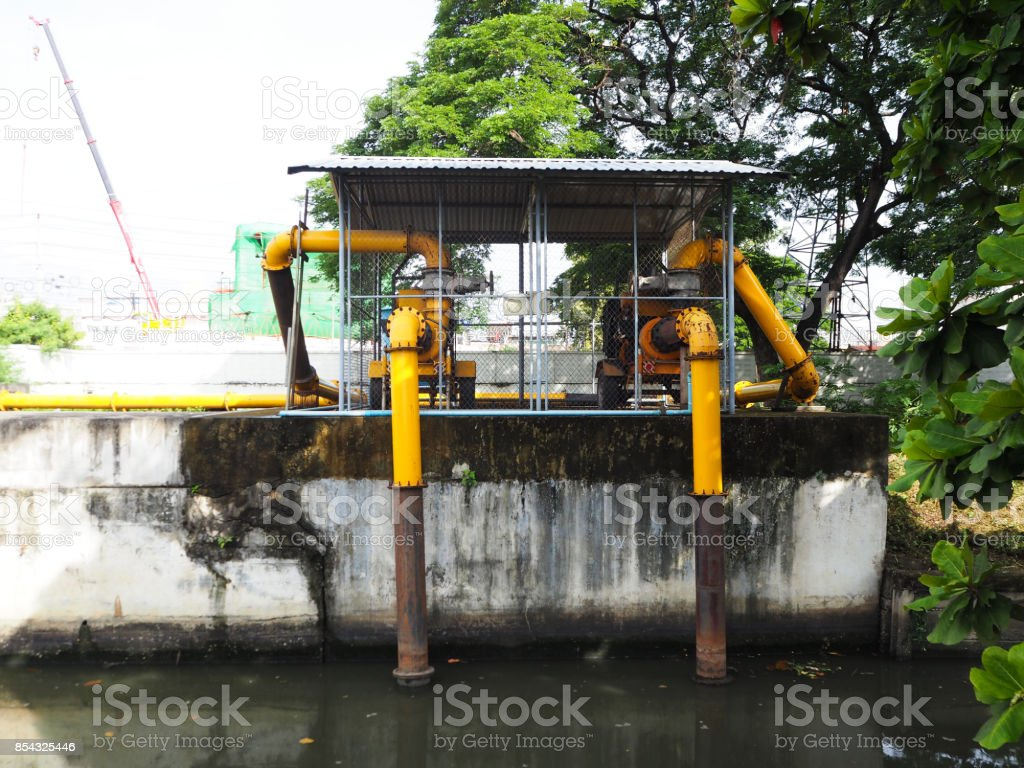 Large industrial water treatment with shiny steel metal pipes and yellow pumps and valves. stock photo
