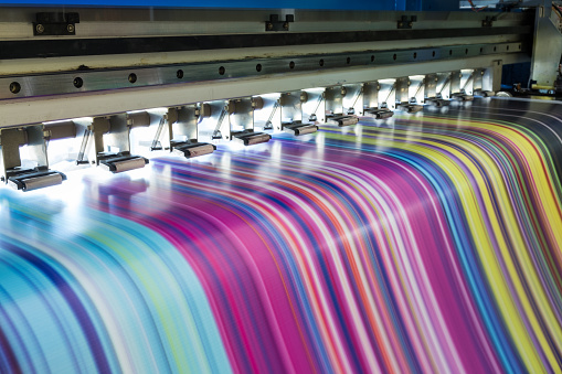 istock Large inkjet printer working multicolor on vinyl banner 869606606