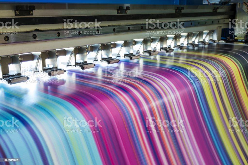 Large inkjet printer working multicolor on vinyl banner stock photo