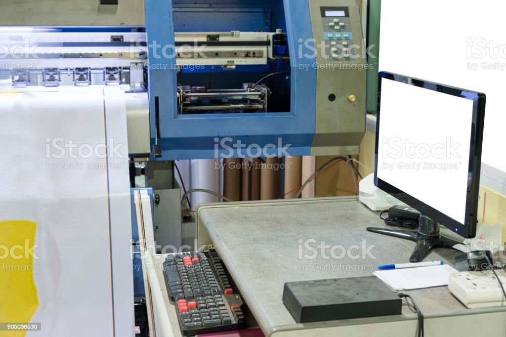 Large inkjet printer working on vinyl banner with computer screen stock photo