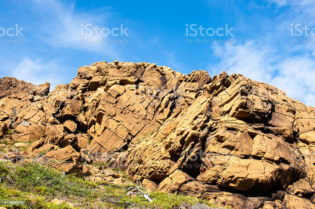 Large irregular cracked rock outcrop against sky stock photo