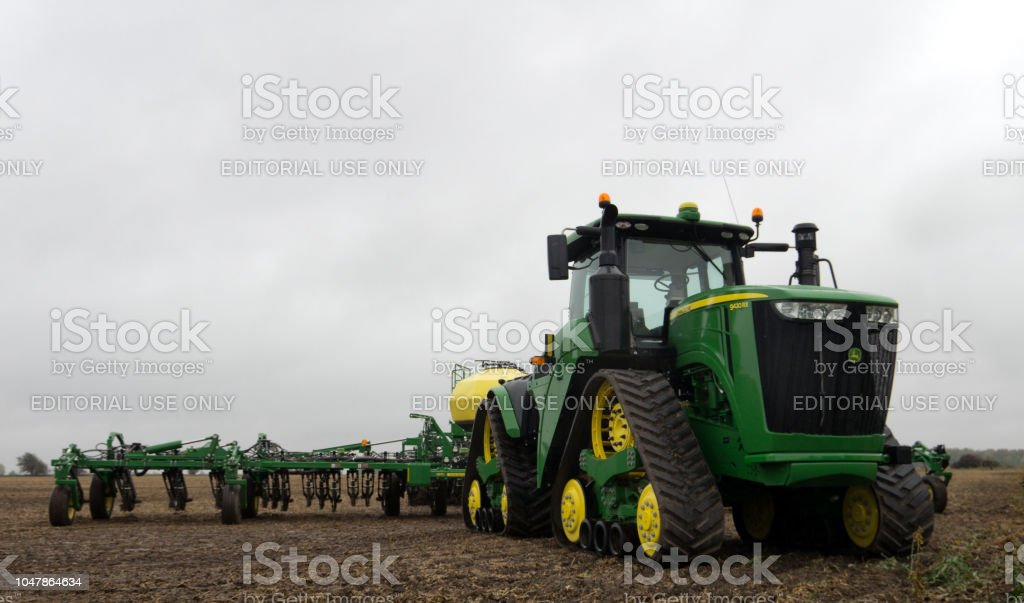 A large green John Deere tractor with equipment used to plant winter...